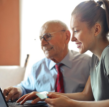 Senior male and young lady sitting at computer making a purchase.